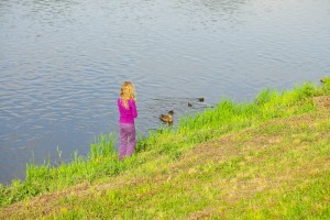 girl looking at ducks